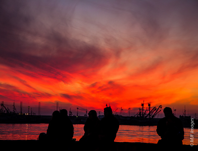 The good citizens of Ensenada, Mexico listen to a Christmas orchestra as the sun goes down over the Pacific.