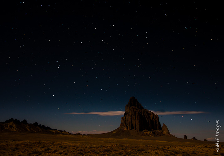 Ship Rock stands under a glowing moon in the northeastern New Mexico desert.