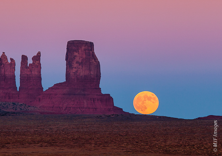 The moon clears the horizon at Monument Valley, Arizona.