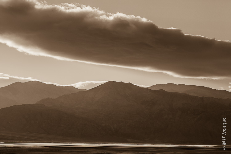 The sun rises and sheds a hard light on the salt flats of Death Valley, leaving the Panamint Range in shadow.