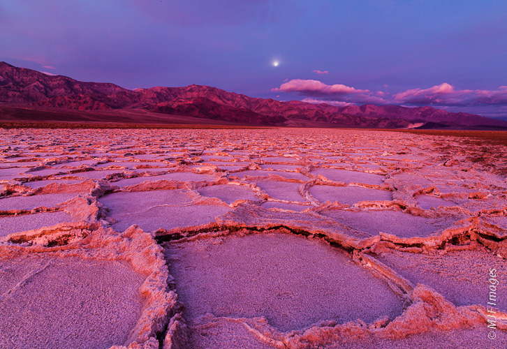 A full moon sets over Death Valley's salt flats as dawn approaches.