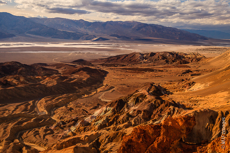 A view of Death Valley from above Artist's Palette shows the playa with its salt pan.  A large alluvial fan is at upper left with dark inselbergs emerging in places.