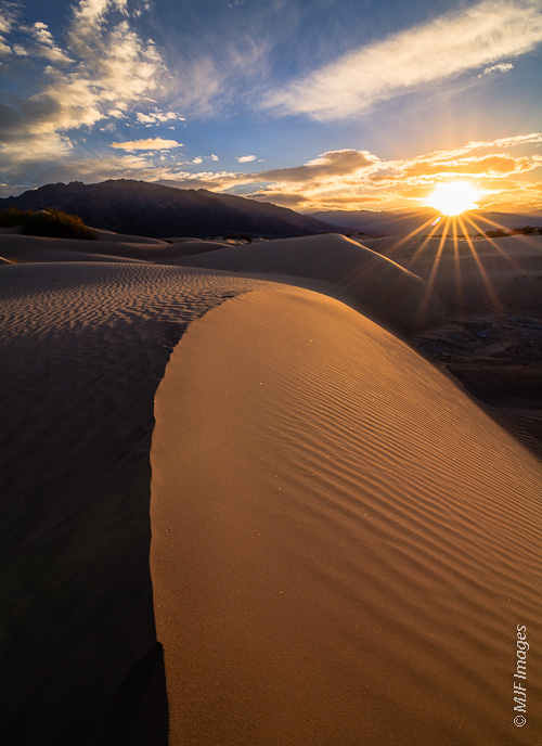 The massive bulk of Tucki Peak looms behind the dunes at Mesquite Flat in Death Valley, California.