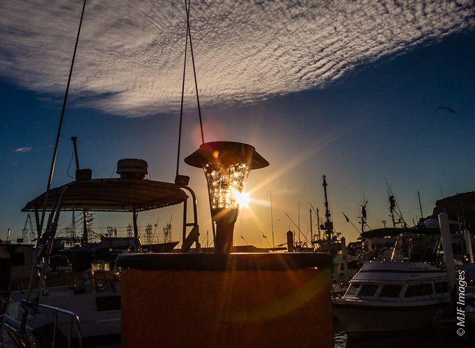 A glass lamp and the setting sun combine to make a miniature lighthouse in Ensenada, Mexico's fishing harbor.