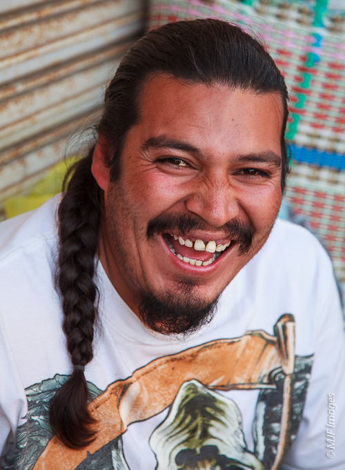 A man selling honey on the streets of Ensenada, Mexico laughs at a friend ribbing him.