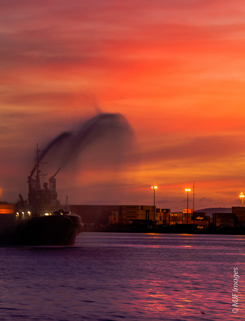 A fire boat sprays water into a colorful dusk sky in Ensenada, Mexico.