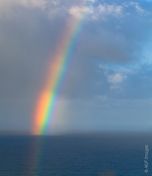 A morning rainbow appears over the Pacific Ocean off the California Coast near Big Sur.