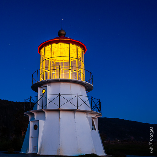 The Cape Mendocino Lighthouse, now restored and located in nearby Shelter Cove, glows just after sunset.
