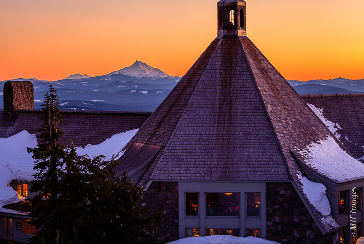 Looking south from Timberline Lodge, the Cascade Range volcanoes stretch away into a clear dusk sky.