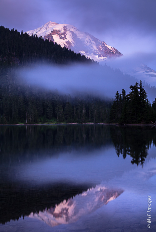 Mount Rainier peaks out above Mowich Lake as the dusk deepens.
