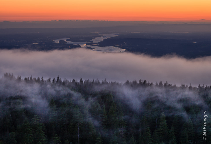 The Columbia River flows west below the foggy forests of the Larch Mountain, Oregon.