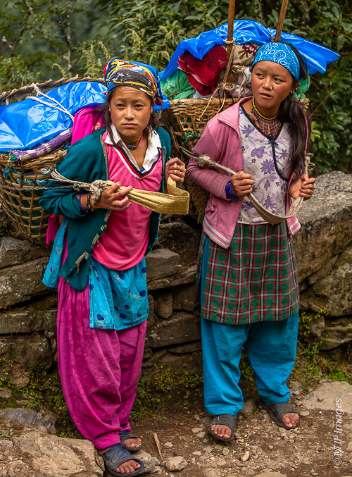 Two young Sherpa girls know nothing but mountain life.  Here they are weary after a long climb hauling heavy loads.