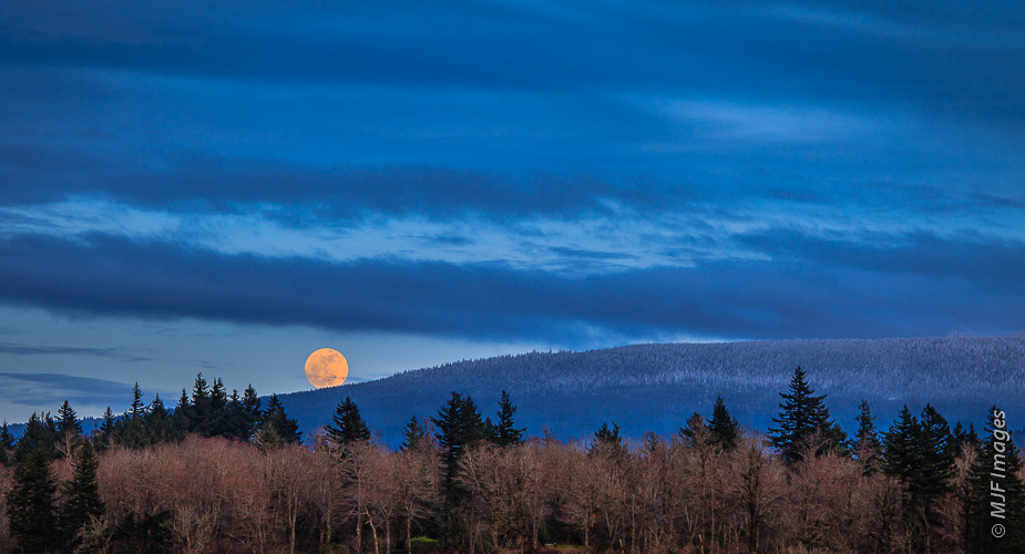 The full moon rises over Larch Mountain at the western end of the Columbia River Gorge in Oregon.