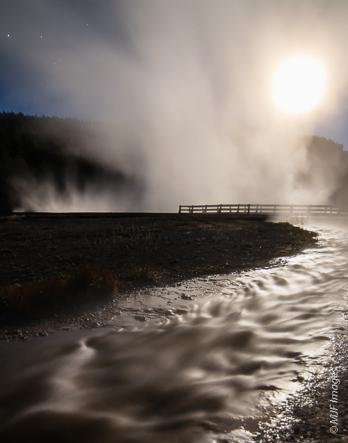 The moon is enlarged through the steam over Hot Lake in Yellowstone National Park.