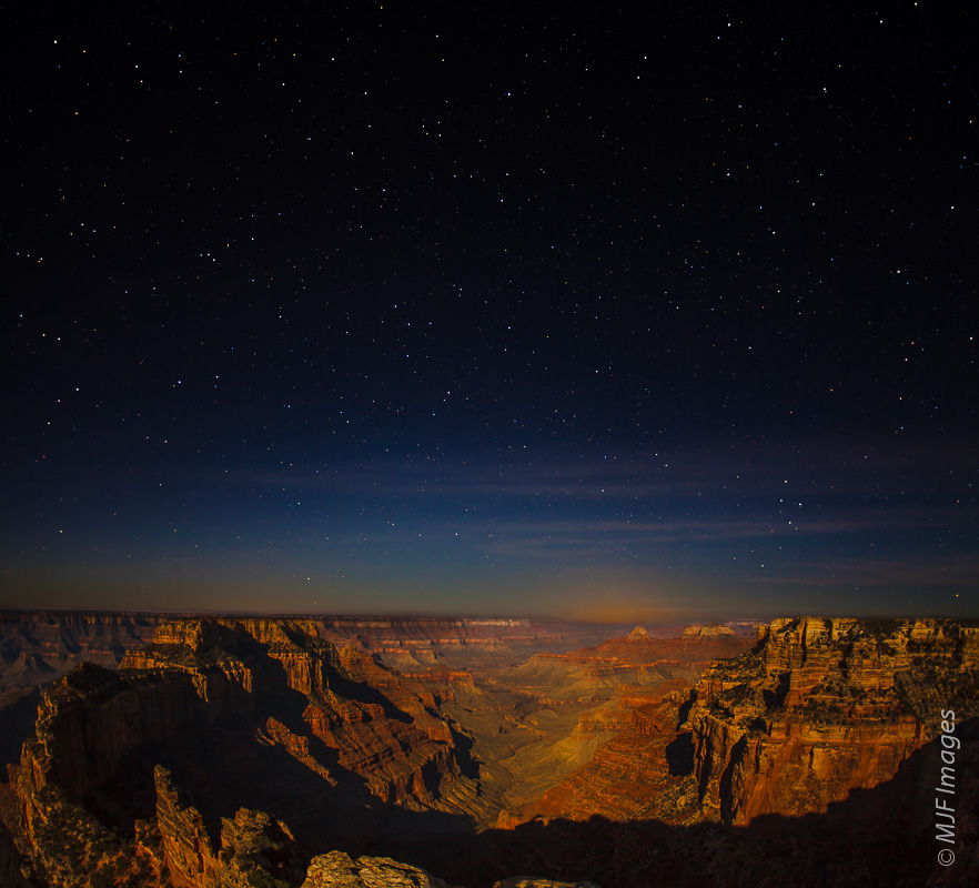 A full moon lights this view from the North Rim westward down the length of the Grand Canyon in Arizona.