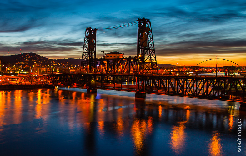 Portland, Oregon is a town of bridges, like the Steele Bridge here spanning the Willamette River at dusk.