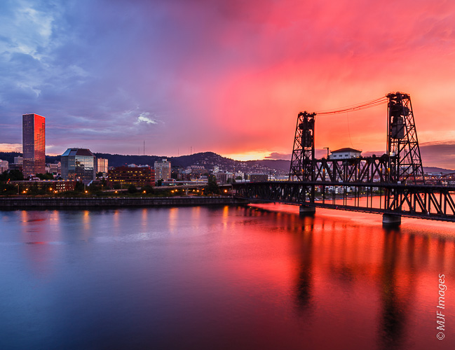 The red light of a stormy sunset illuminates the Willamette River as it flows under the Steele Bridge in Portland, Oregon.