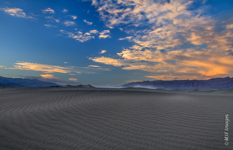 A small windstorm sweeps sand and dust down Death Valley toward the sand dunes.