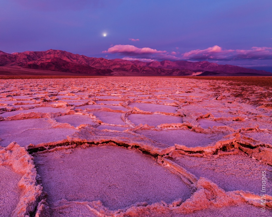 A full moon sets over Death Valley's salt flats as a pink dawn approaches.