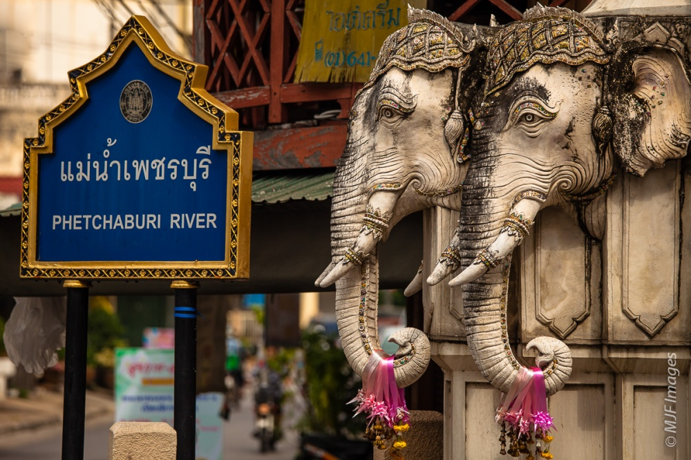 A bridge abutment in Thailand is carved into elephant heads.