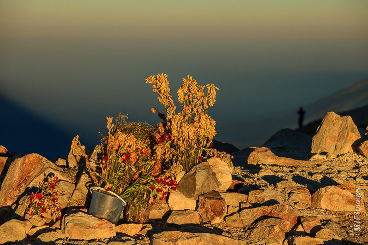 Offerings at the summit of Tajamulco, Guatemala.  A lone climber stands in the shadow of the mountain.