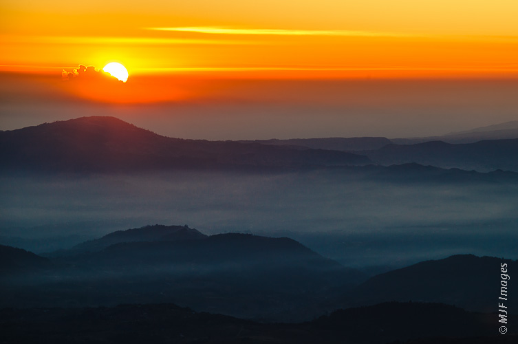 The sun rises over the Guatemalan highlands, as viewed from the summit of the highest mountain in Central America, Tajamulco.