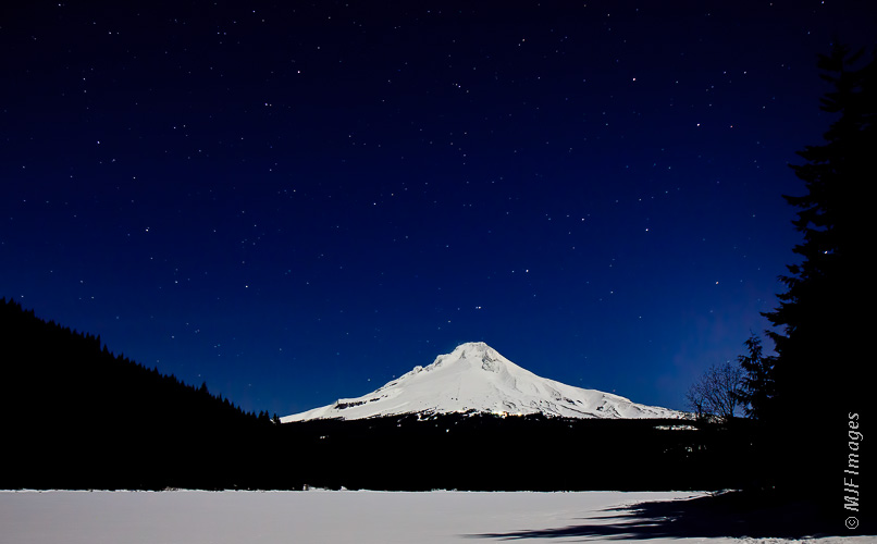 Mount Hood stands near snow-covered Trillium Lake on a full moon ski.