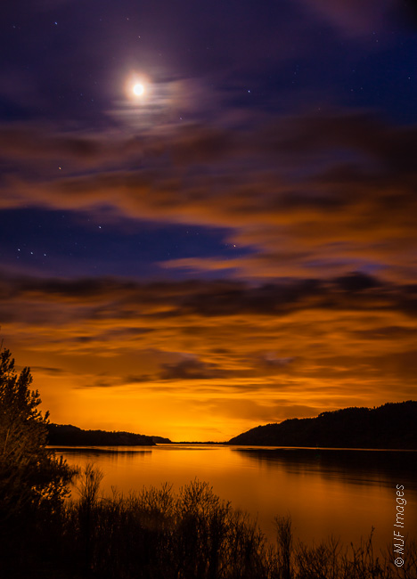 The Columbia River flows west toward the sea in deep evening as the moon shines above.