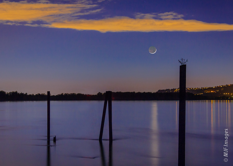 A thin crescent moon over the Columbia River, Oregon. Composite of two images: Background - 110 mm., 30 sec. @ f/11, ISO 400; Moon - 200 mm., 3.2 sec @ f/4, ISO 400.