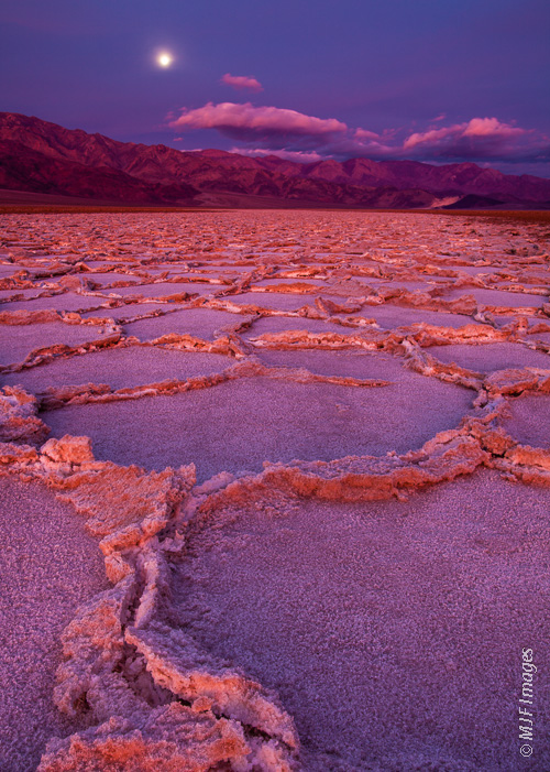 The full moon sets just as morning light hits the cracked salt flats near Badwater, North America's lowest point, in Death Valley, California.