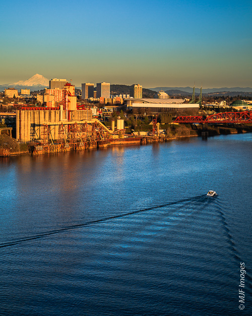 The Willamette River flows past Portland's port area with Mount Hood standing in the background.