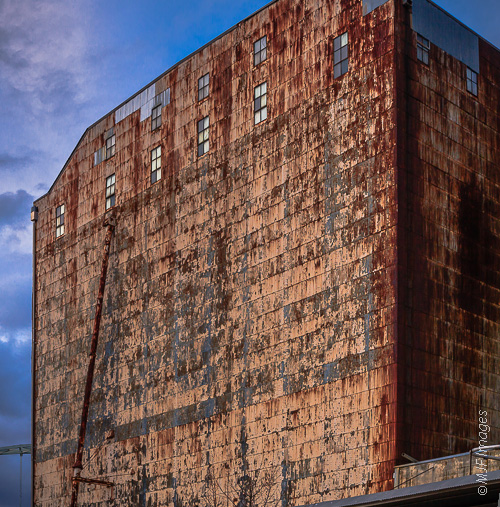 A large warehouse, now in disuse, shows off its huge textured wall at Portland, Oregon's old rail station.