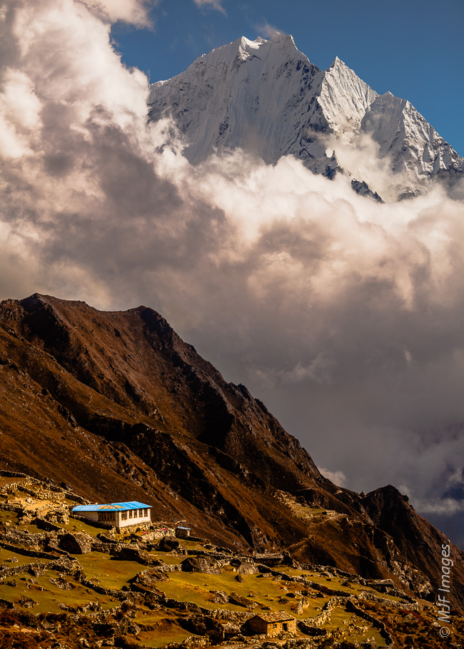 Photographed at an angle to the setting sun, a lone farmstead in the Khumbu region of Nepal's HImalayan Mountains lies in spectacularly rugged country.
