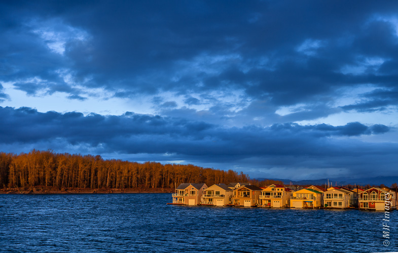 Houses over the water in the Columbia River in Oregon have beautiful views westward to the setting sun.