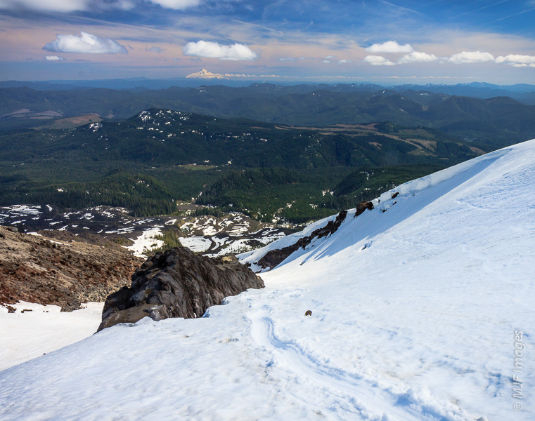 The glissading track formed in the snow from climbers descending Mount St. Helens.  Mount Hood is visible in the distance.