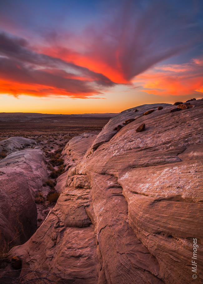 The desert sun sets over the ubiquitous sandstone outcrops that surround Page, Arizona.