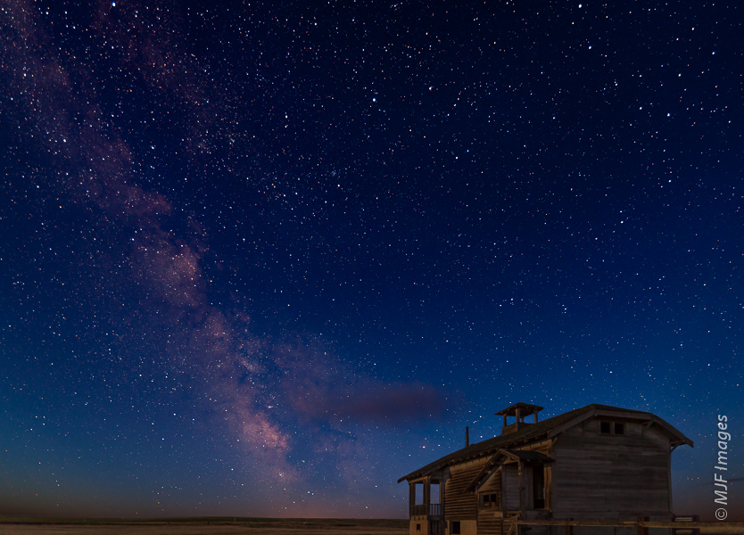 An old abandoned schoolhouse out on the Oregon prairie is illuminated by a crescent moon.  The Milky Way glows pink in the coming dawn.