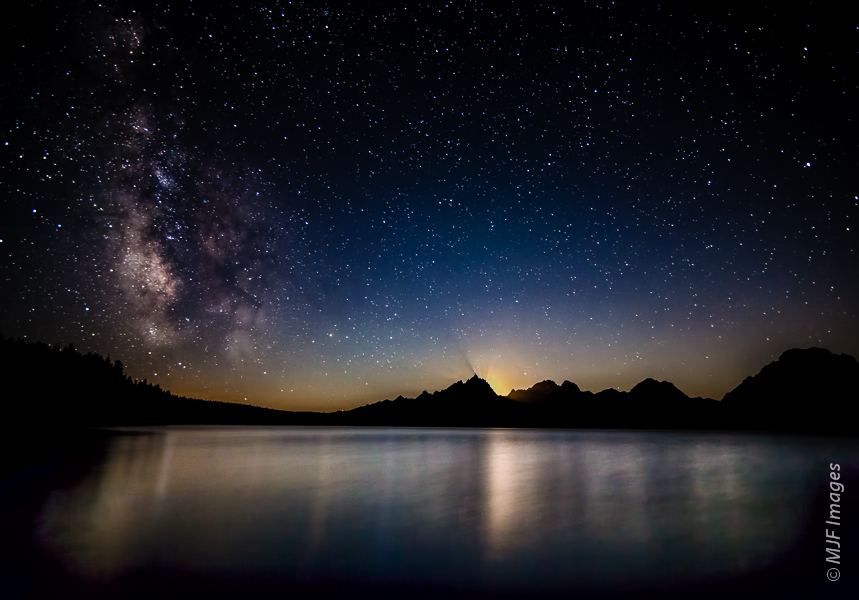 The moon sets behind the Tetons as the Milky Way soars over Jackson Lake, Wyoming.