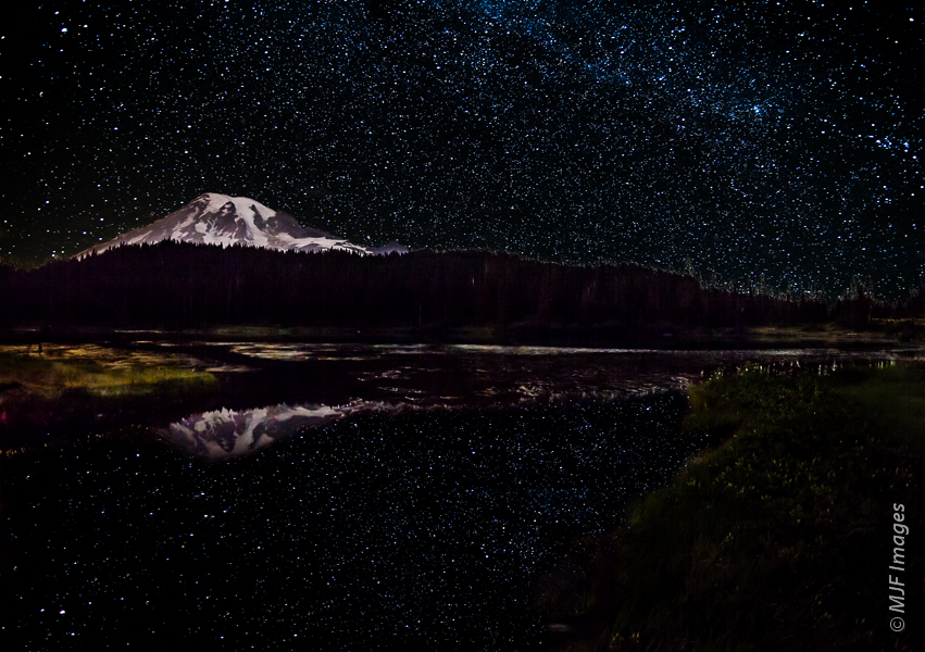 The starry sky on a clear evening is reflected in the aptly-named Reflection Lakes at Mount Rainier National Park in Washington.