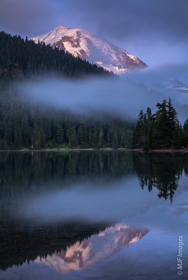 The clouds rapidly flow out of the basin containing Mowich Lake as night comes on and temperatures drop, revealing Mount Rainier standing above.