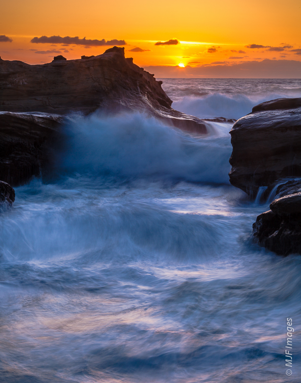 Golden light from a setting sun is reflected from the churning, flowing surf at Cape Kiwanda on the Oregon Coast.