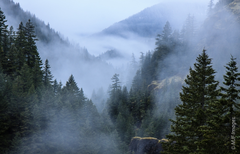 The rugged Salmon River Canyon of western Oregon is mantled in clouds and dusted with a late-season snowfall.