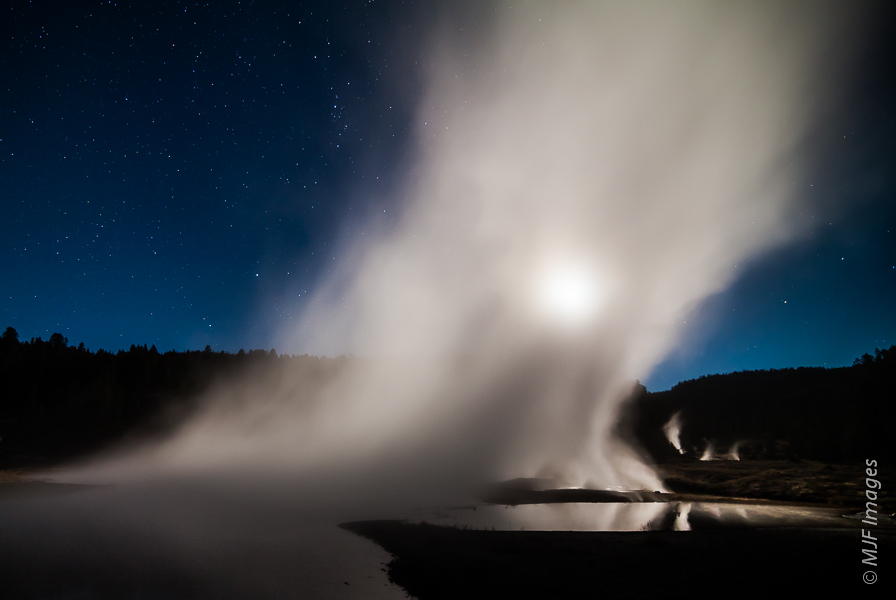 The full moon as viewed through a translucent veil formed by geothermal steam at Firehole Lake in Yellowstone National Park.