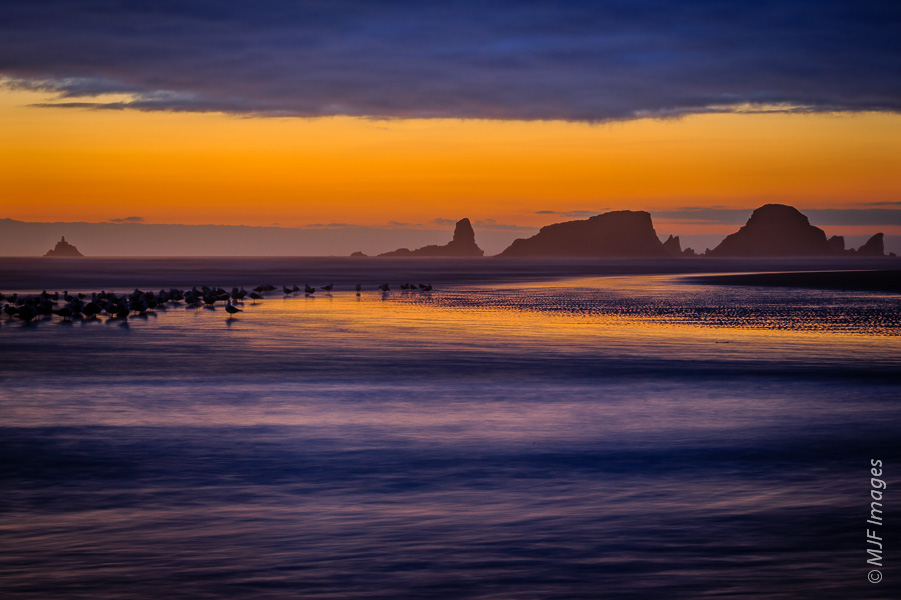 The sea stacks just offshore of Cannon Beach, Oregon are set against a peaceful summer sunset.
