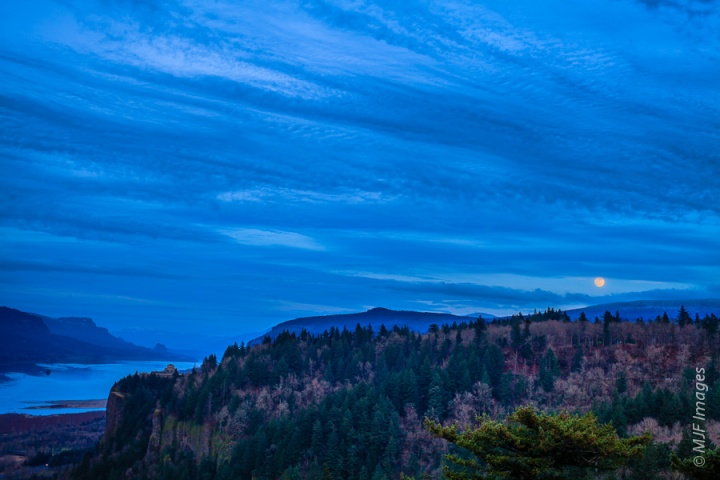 The full moon rises over Crown Point and the Columbia River Gorge in Oregon.