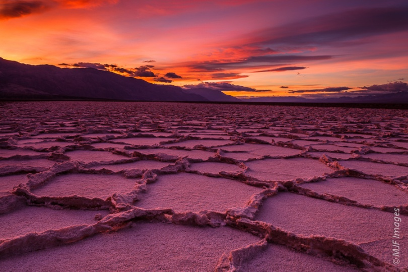This picture in Death Valley, California is directed at an angle to the setting sun.  It takes advantage of red-orange light reflected (and refracted) by the clouds back down on the salt flats.  The salt in turn reflects the light, but with a unique tinge created by interaction of the warm light with the salt crystals.