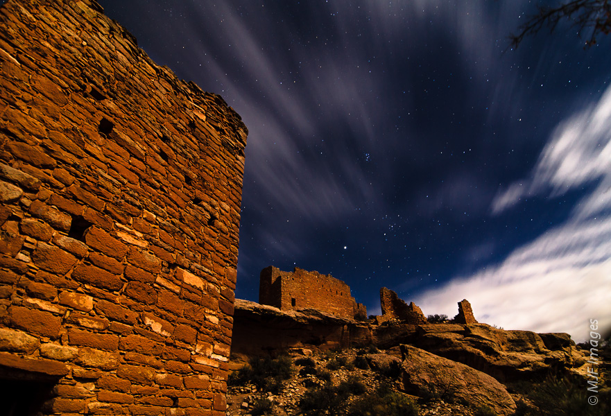 Fast-moving clouds streak the sky over moonlit Little Ruin Canyon at Hovenweep, Utah.