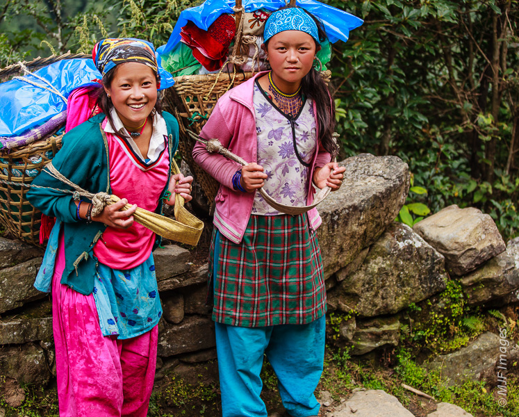 Two young Sherpa friends haul equipment on the trail to Namche Bazaar in Nepal.