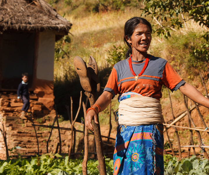 A woman in the Himalaya of Nepal is proud of her vegetable garden, and her grandson.
