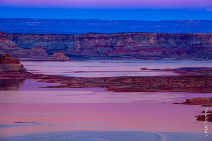 A lone jet skier motors across Lake Powell, Arizona at dusk.